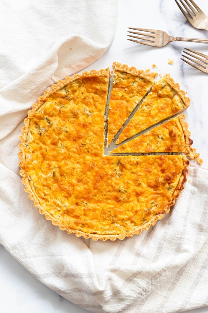 an overhead shot of a quiche tart resting on a white dish towel. three wedges have been cut out of the top right quadrant of the quiche.