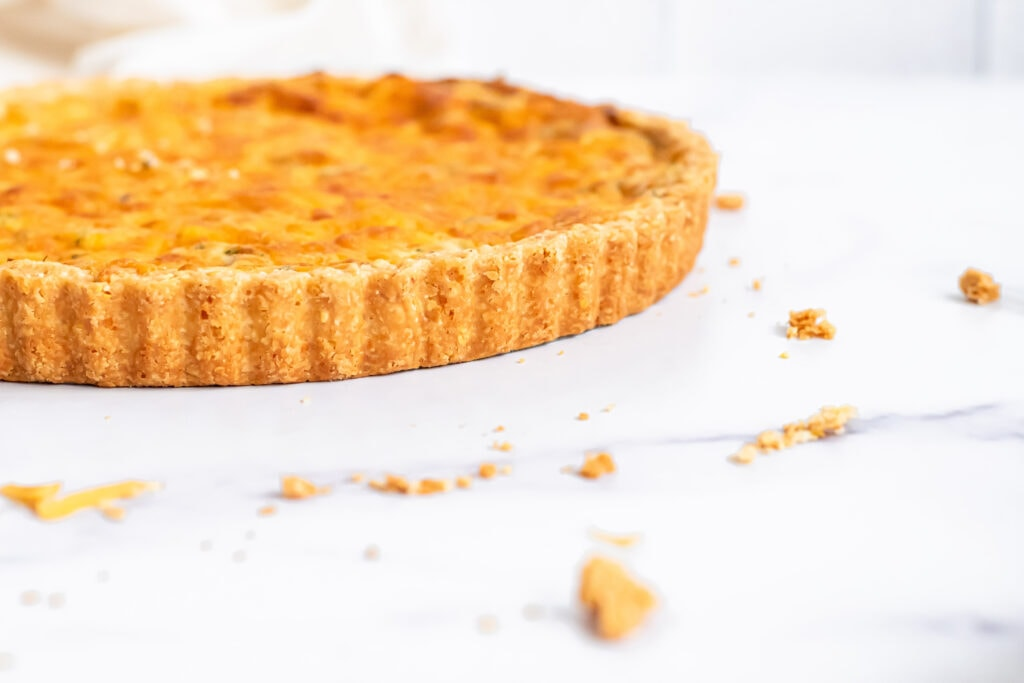 a low angle photo of a quiche. half the quiche is cropped out of the left side of the frame.