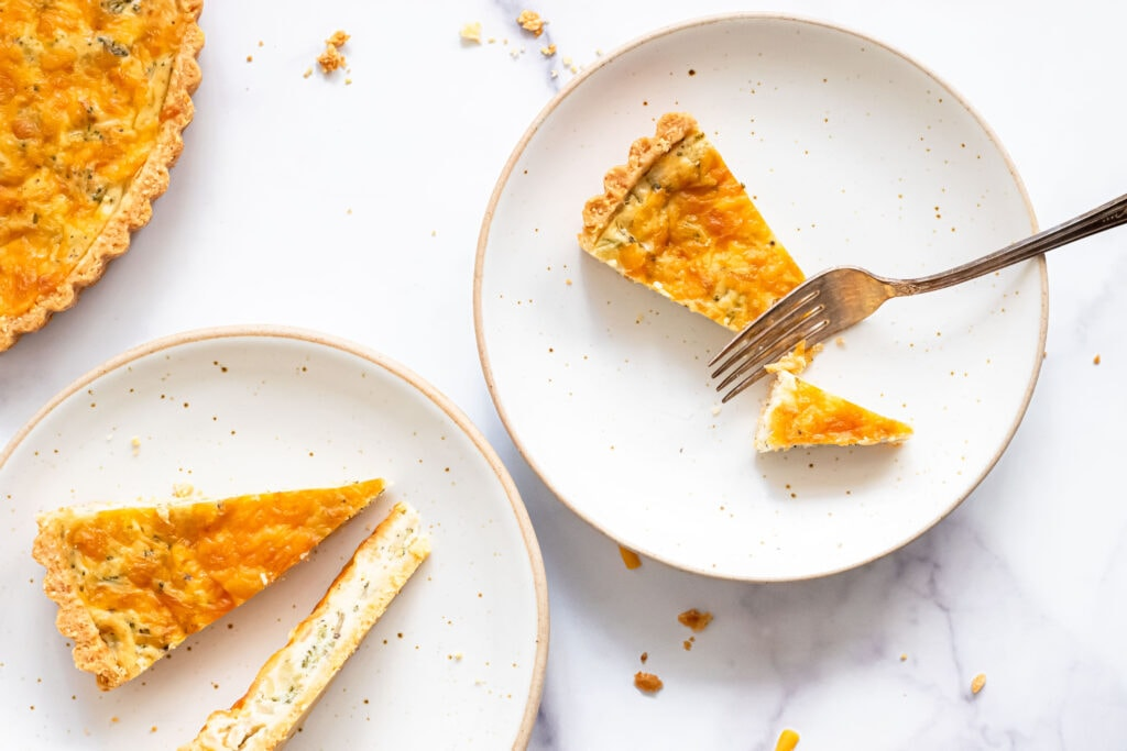 an overhead shot of two white plates with slices of quiche tart on them. one of the slices has been cut in half with a fork, which is resting on the plate.