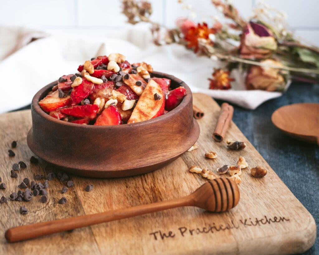 a wooden bowl of fruit salad sits on a wooden board. a wooden honey wand lies in front of it. nuts are scattered on the board next to the bowl. a bouquet of dried flowers lies on the table behind it.