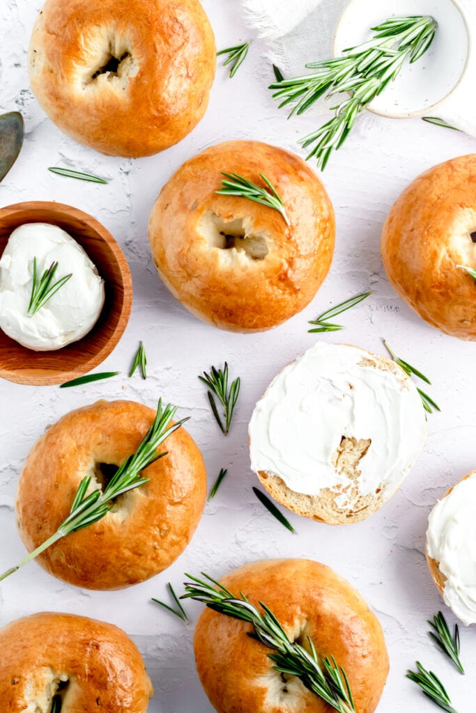 an overhead shot of rosemary bagels lying flush against each other. one bagel in the center has been elevated closer to the lens and is more in focus than the bagels around it. the very edges of a rosemary plant are creeping in from the right side of the photo.