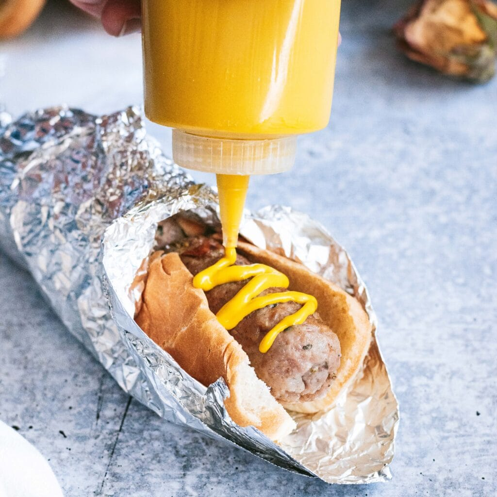 a close up of a sausage in a hot dog bun wrapped in aluminum foil. a squeeze bottle of yellow mustard is inverted over it squirting a zig zag of mustard onto the sausage.