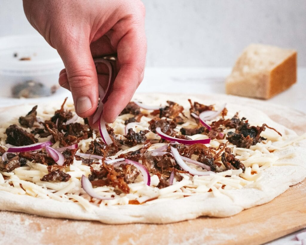 a side view of a hand putting sliced onion on a bbq pizza sitting on a pizza peel before being baked. a wedge of parmesan cheese is visible in the background.