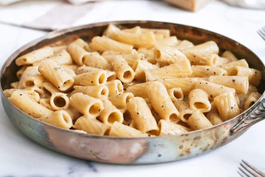 a close up of a skillet with cacio e pepe rigatoni flecked with pepper and shiny melted cheese