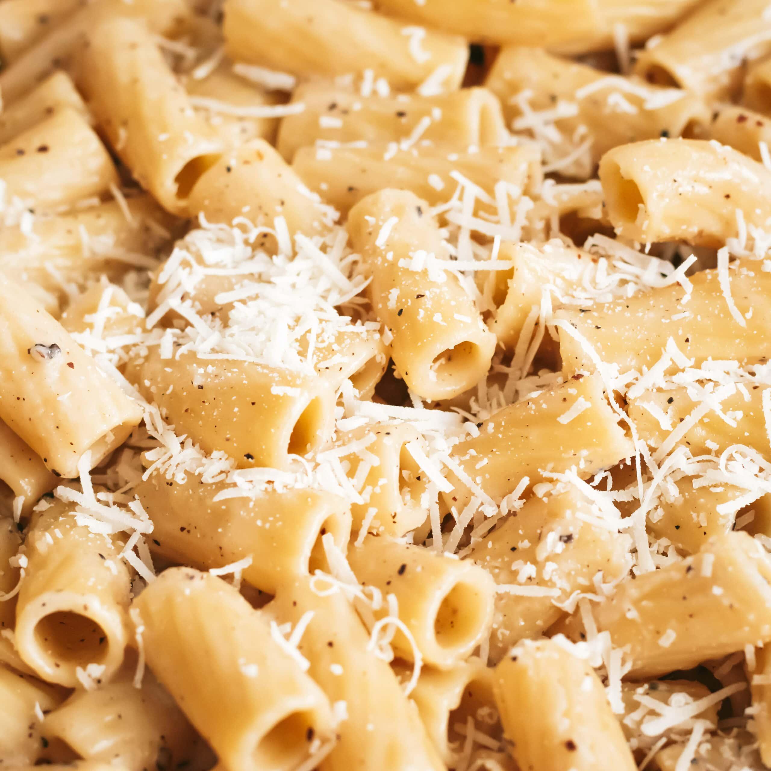 a close up of cheesy cacio e pepe rigatoni topped with grated pecorino and parmesan cheese