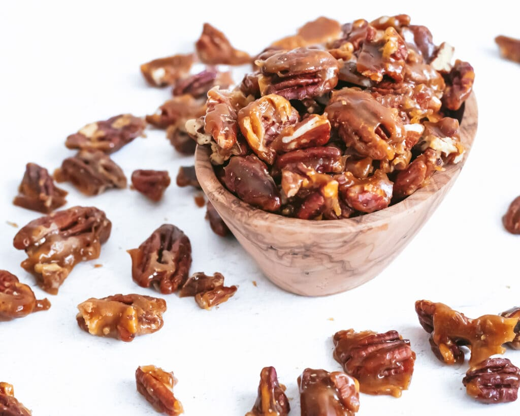 a close up photo of a small wooden bowl filled with candied pecans, some of which have spilled over onto the counter